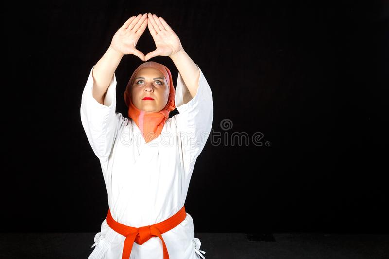 Young Muslim woman in kimono and hijab in karate exercises. Shooting close-up. Young Muslim woman in kimono and hijab in karate exercises. Shooting close-up royalty free stock photos
