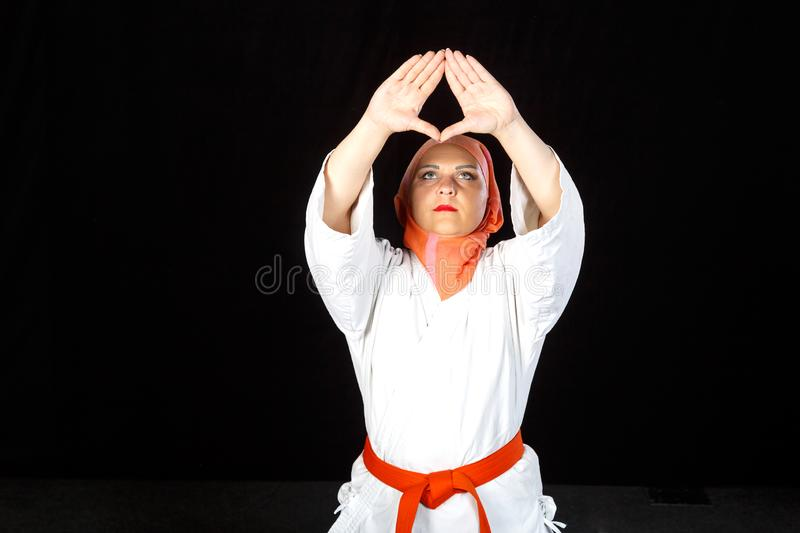 Young Muslim woman in kimono and hijab in karate exercises. Shooting close-up. Horizontal photo royalty free stock images