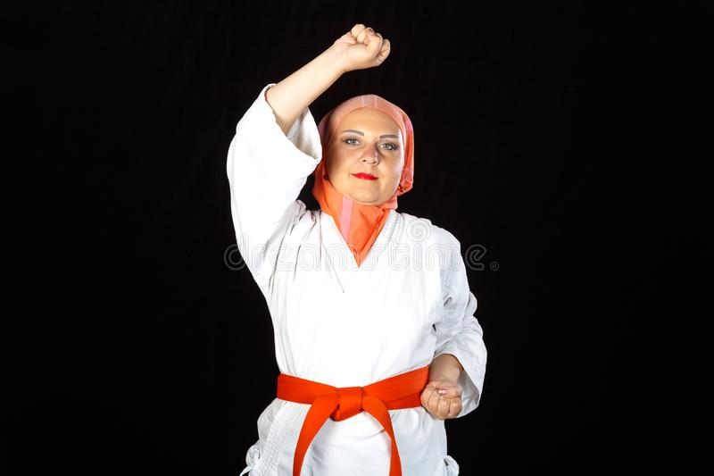 Young Muslim woman in kimono and hijab in karate exercises. Horizontal photo royalty free stock photos