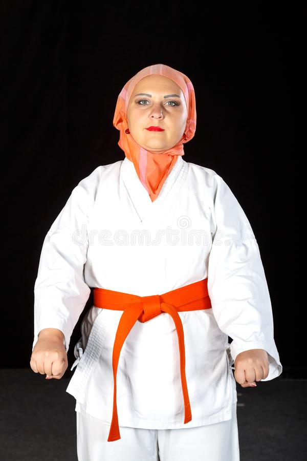 Young muslim woman in kimono and hijab in karate training over black background. Shooting close-up. Vertical frame stock image