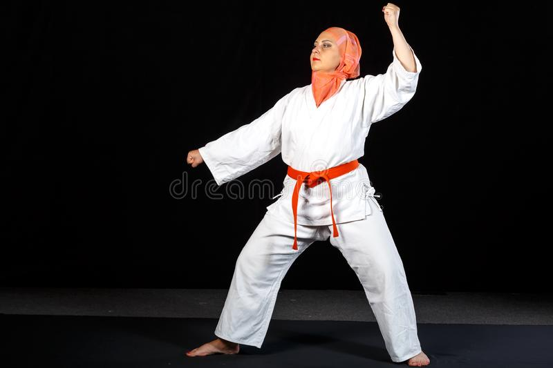 Young muslim woman in kimono and hijab in karate training over black background. Horizontal photo stock image