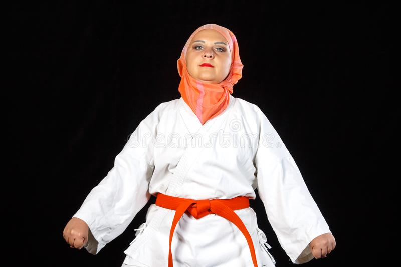 Young muslim woman in kimono and shawl during karate training over black background. Shooting close-up. Horizontal photo royalty free stock photography