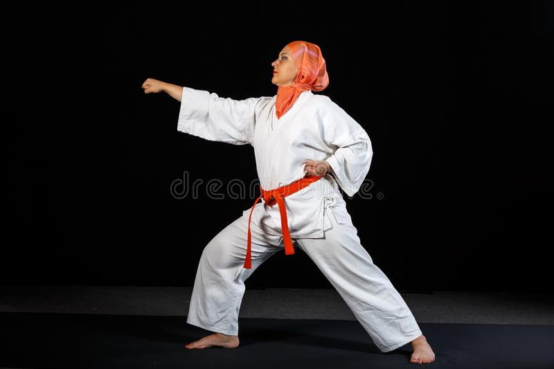 Young muslim woman in kimono and shawl during karate training over black background. Horizontal photo royalty free stock photo