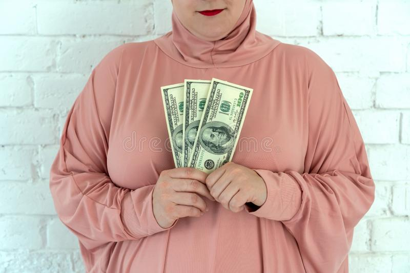 Young muslim woman in pink hijab clothes hold of cash money in dollar banknotes and rosary in her hands royalty free stock photos