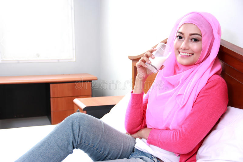 Young muslim woman relax on bed and drinking a glass of milk royalty free stock image