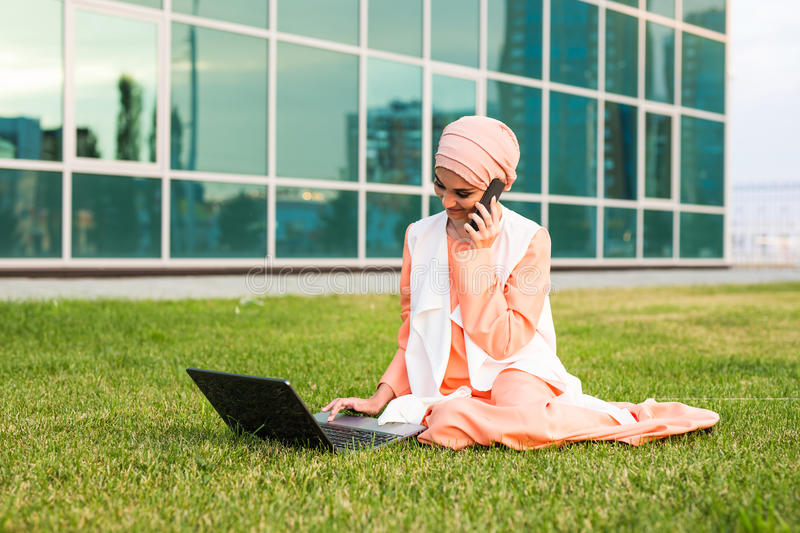 Young Muslim Woman Using Mobile Phone and Laptop In Park stock photos