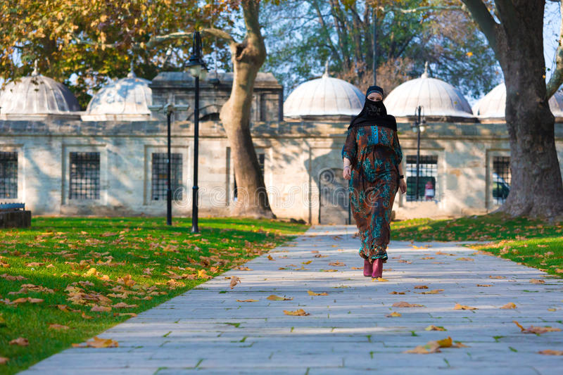 Young Muslim Woman walking in park. An attractive Young woman wearing a colorful head covering and Muslim Dress Walking on Alley in Autumnal Yard of Mosque stock image