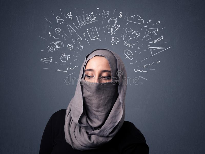 Muslim woman wearing niqab. Young muslim woman wearing niqab with mixed white drawings above her head royalty free stock image