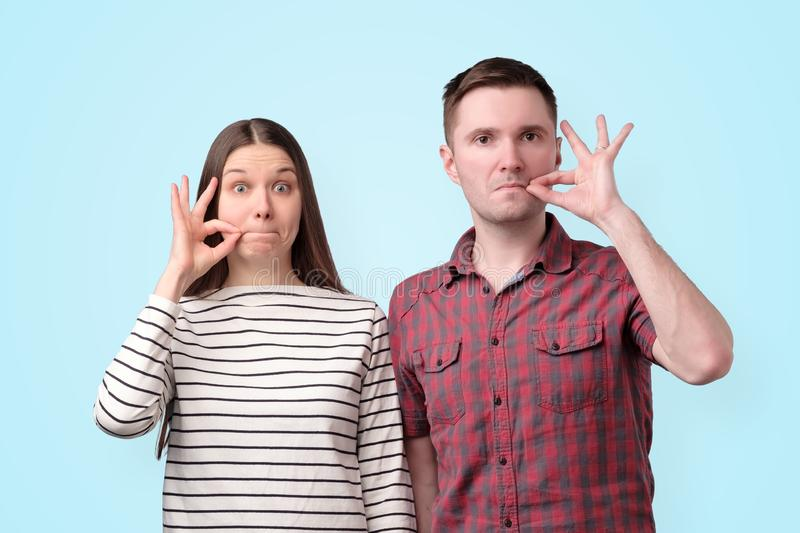 Young mute couple holding fingers on lips like zipper to keep secret for conspiracy stock images