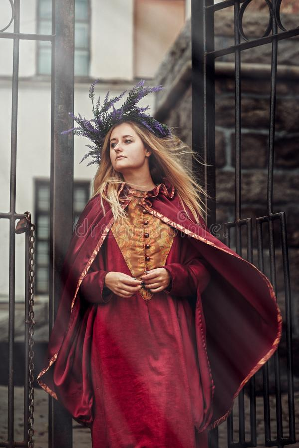 A young mysterious girl in a historical costume is between the gates of the castle stock image
