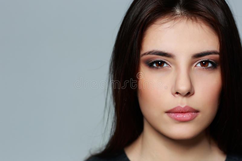 Young mysterious woman on gray background royalty free stock image