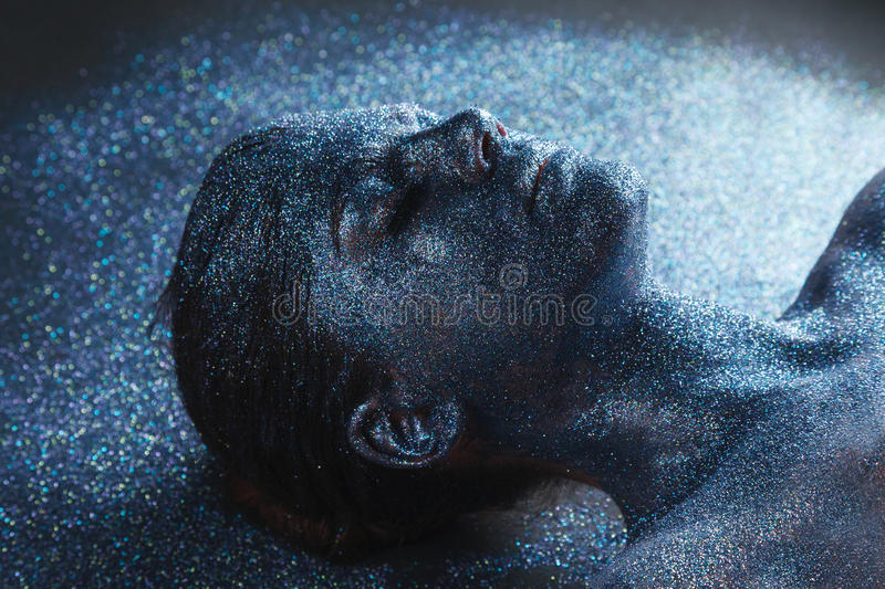 Young mystical fantasy woman from another world. Portrait of young mystical fantasy woman from another world covered with tinsels lying on her back on a floor stock photo