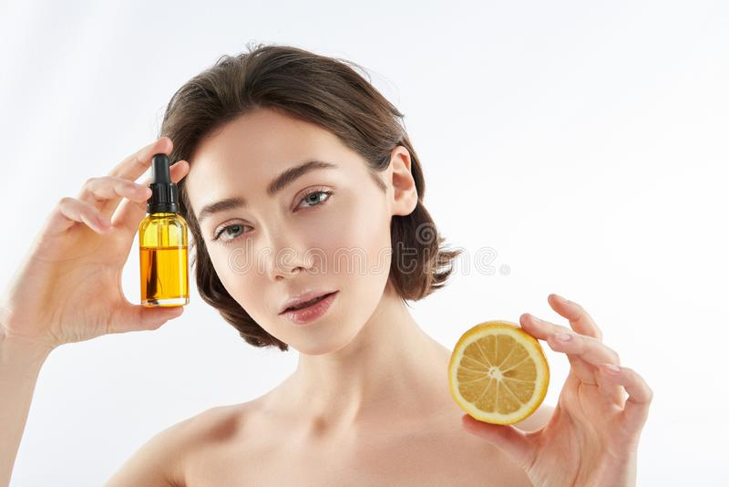 Young naked female with lemon and oil bottle stock photo