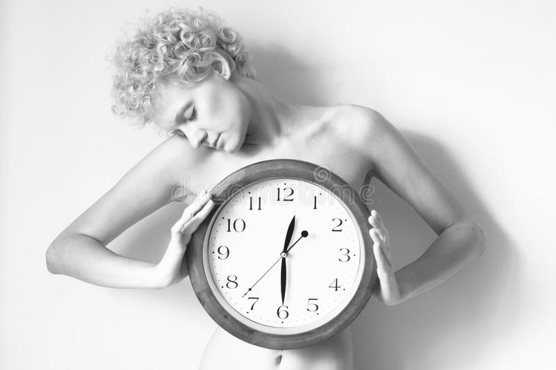 Young naked girl with curly hair standing holding a big clock. Black and white photography. Conceptual photo about the mode of the day stock images