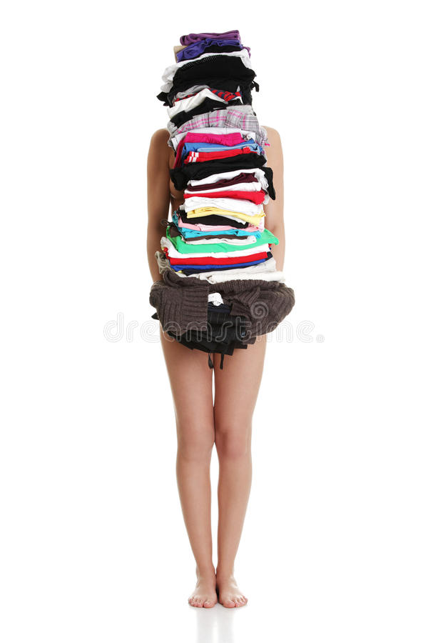 Young naked woman is standing and holding clothes. royalty free stock image