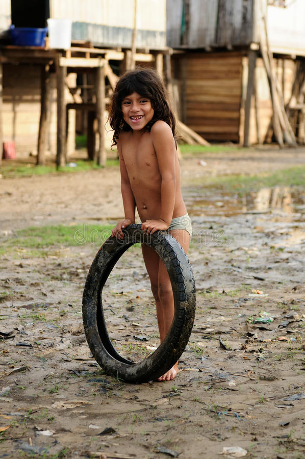 Young Native American from the Amazonian jungle. PERU, AMAZONIA - JUNE 23: Young Native American playing with the tyre in his village in the Amazonian jungle in royalty free stock photo