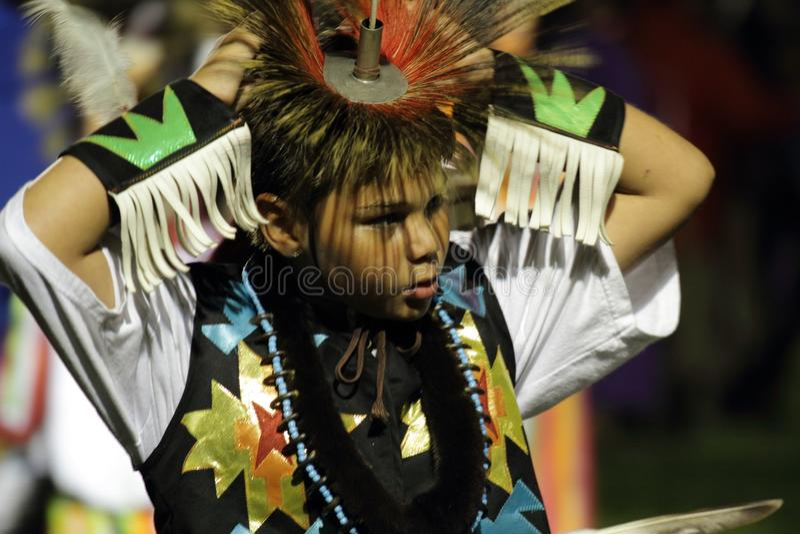 Young Native American boy adjusts headdress