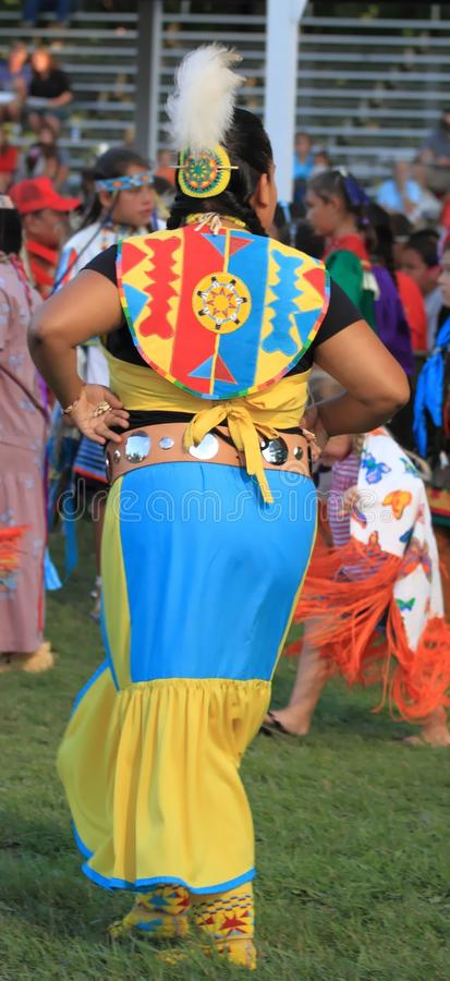 Young Native American woman dancing in regalia. Young woman dancing in full regalia at the Meskwaki Pow Wow in Tama, Iowa, 2012 shot from behind royalty free stock images