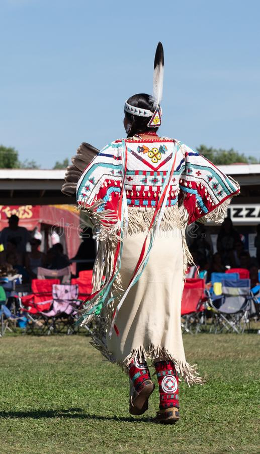 Young Native American Woman Dancing in Pow Wow with Beaded Leather Dress. Young Native American woman pow wow dancer with leather dress with beadwork, elks` stock photos