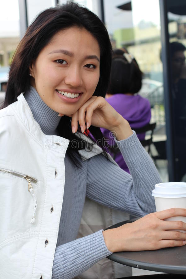 Young natural Asian woman sitting at a cafe stock photo