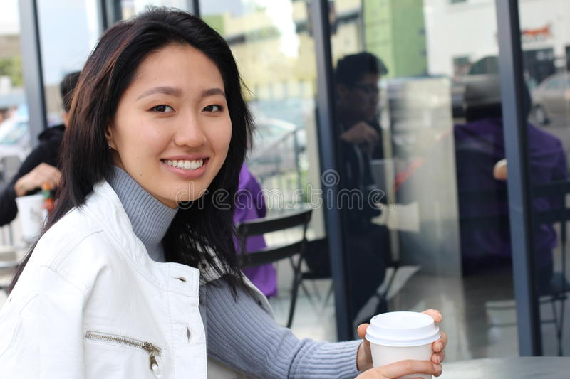 Young natural Asian woman sitting next to windows in cafe stock photography