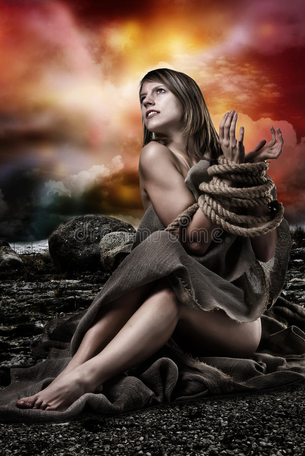 Woman with tied up hands. Young, natural beauty blond woman are tied up with rope. She is sitting half naked, covered with canvas material. Looking up to the stock photos