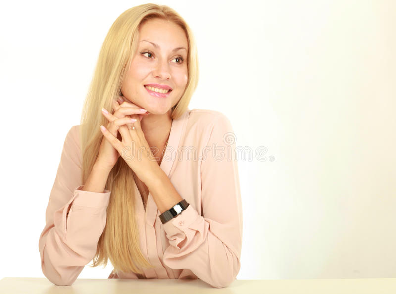 Young natural woman with clean face sitting at white table leaning on her elbows, over background. Young natural woman with clean face sitting at white table royalty free stock images