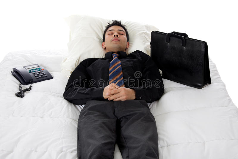 Young Nepalese businessman, nap. Young Nepalese businessman in bed taking a nap between telephone and suitcase. Studio shot. White background stock photos