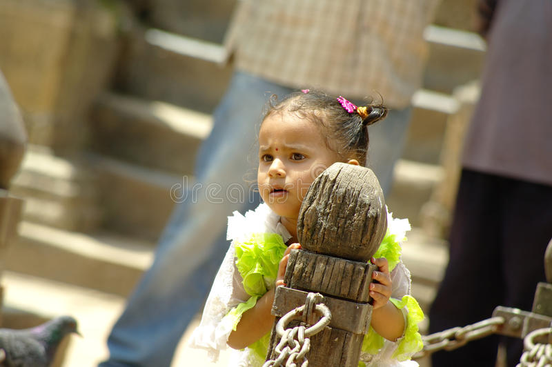 Young Nepalese girl hide from her mother in Durbar square. stock images