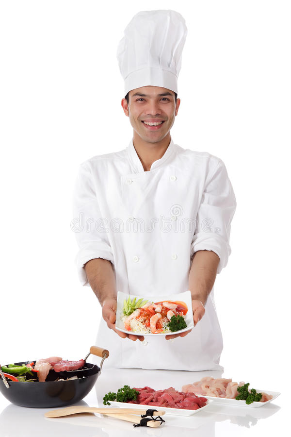 Young nepalese man chef, oriental food. Young cheerful nepalese man showing a plate with oriental food. Wok with ingredients and raw meat on table Studio shot stock photo