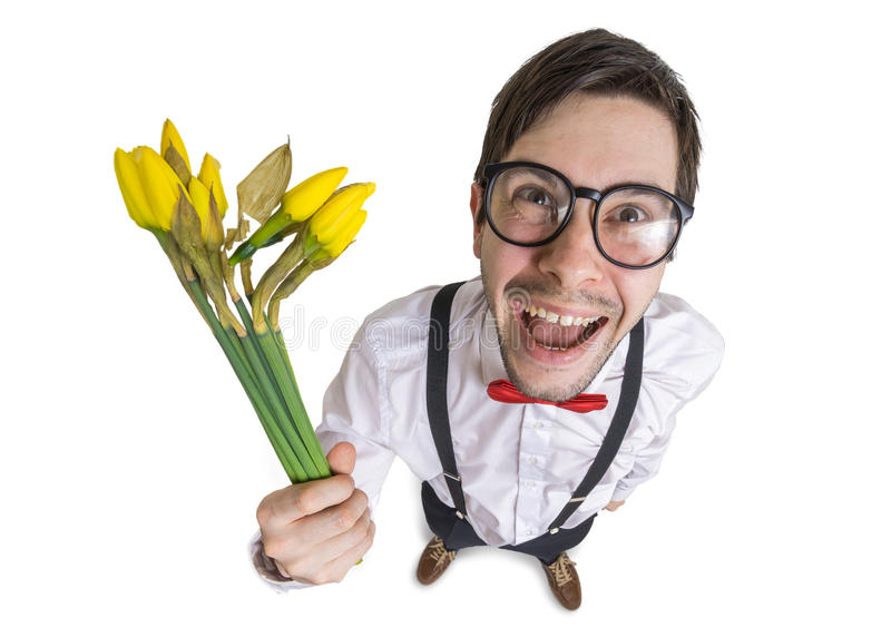 Young nerdy man holds blossoming yellow flowers in hand at first date. Isolated on white background.  stock photography