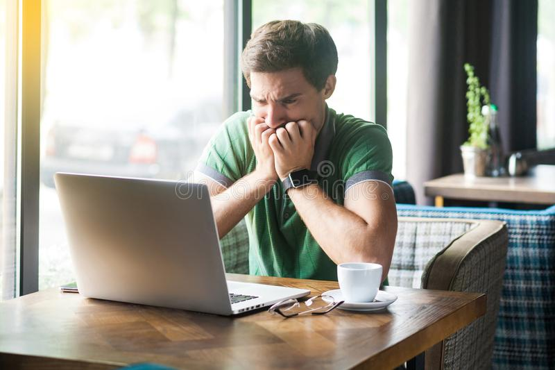 Young nervous businessman in green t-shirt sitting and working on laptop, bitting his nails and looking at screen with worry face stock image