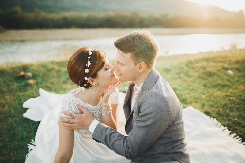 Young newly wed couple, bride and groom kissing, hugging on perfect view of mountains, blue sky.  royalty free stock images