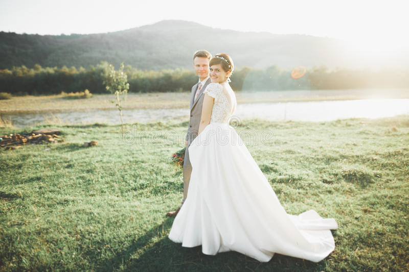 Young newly wed couple, bride and groom kissing, hugging on perfect view of mountains, blue sky.  stock photo