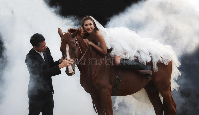 Young newlywed couple, beautiful beauty bride in fashion white bridal wedding costume riding on strong muscular horse standing by stock photography