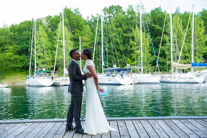 A young newlywed couple on dock at marina. A young newlywed couple on a dock at marina hugging and kissing on wedding day stock photos