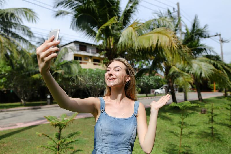 Young nice girl making video call by smartphone near palm trees in background. Young pretty girl making video call by smartphone near palm trees in background royalty free stock images