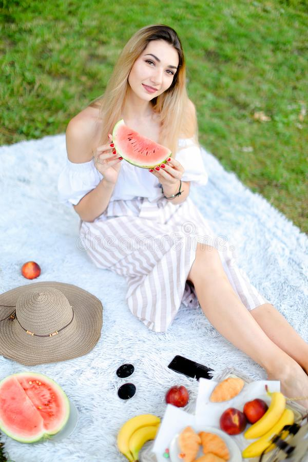 Young nice girl sitting on plaid near fruits and hat, eating watermelon, grass in background. stock images