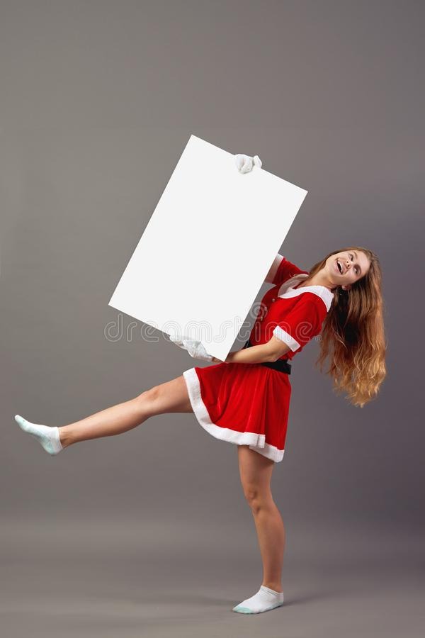 Young nice mrs.Santa Claus dressed in the red robe, white gloves and white socks rises up a white canvas on the gray royalty free stock photography
