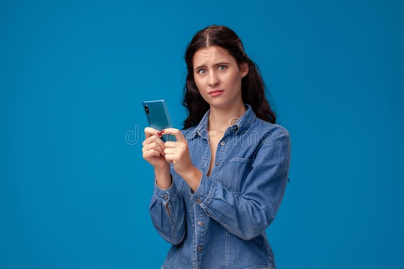 Young brunette woman is posing with a smartphone standing on blue background. royalty free stock images