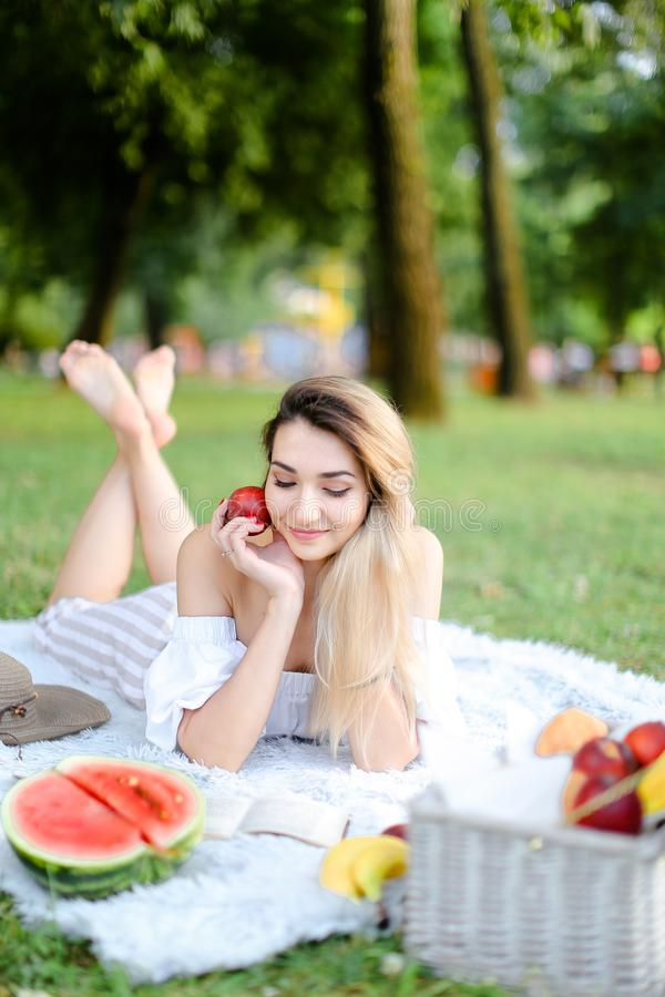 Young nice woman lying on plaid in park, reading book near watermelon and keeping apple. royalty free stock photo