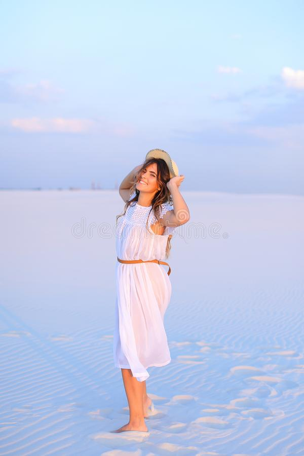 Young nice woman wearing dress and hat standing on white sand in stock photo