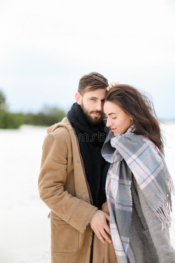 Young nice woman wearing grey scarf standing with man in coat, winter white background. Young nice women wearing grey scarf standing with men in coat, winter royalty free stock images