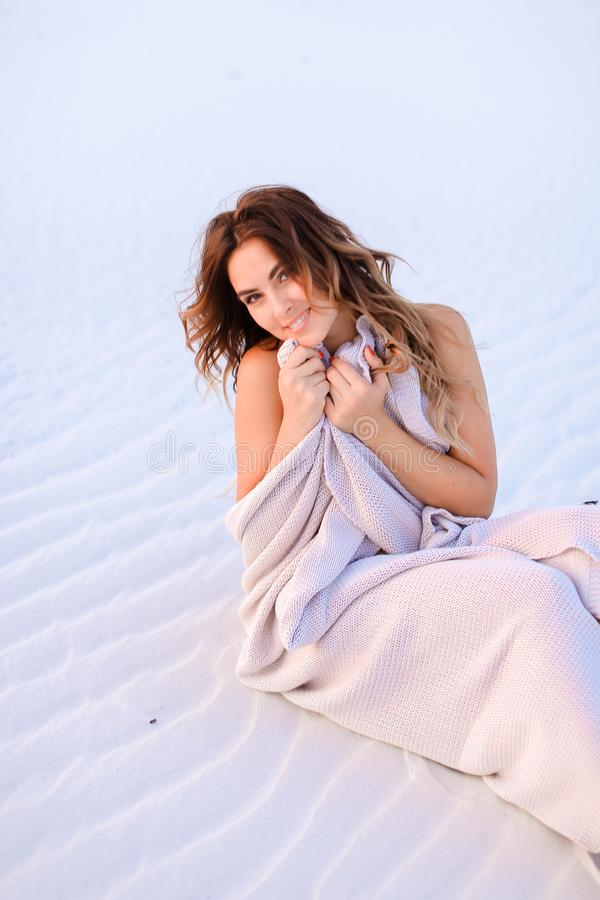 Young nice woman wrapped in blanket sitting on white sand. stock photography