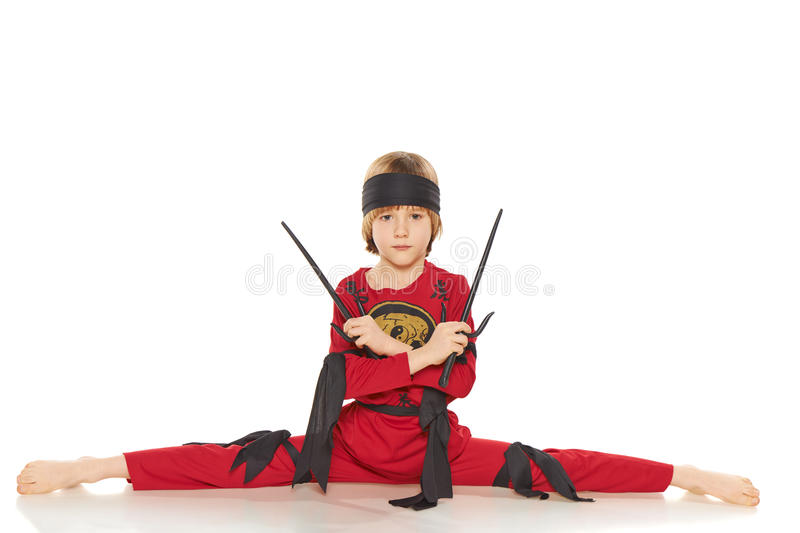 Young Ninja. Doing the splits and holding sabres over white background stock photography