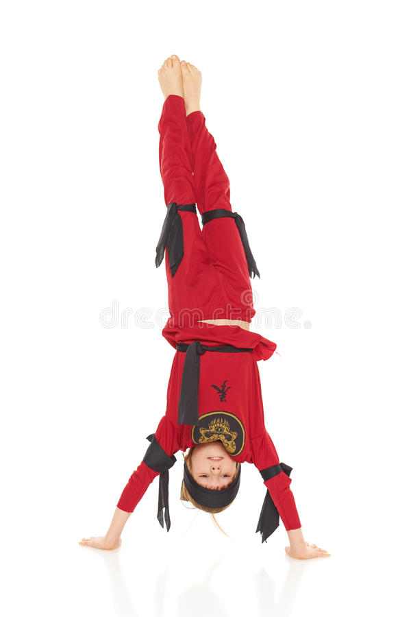 Young Ninja. Standing on hands, front view, over white background royalty free stock image