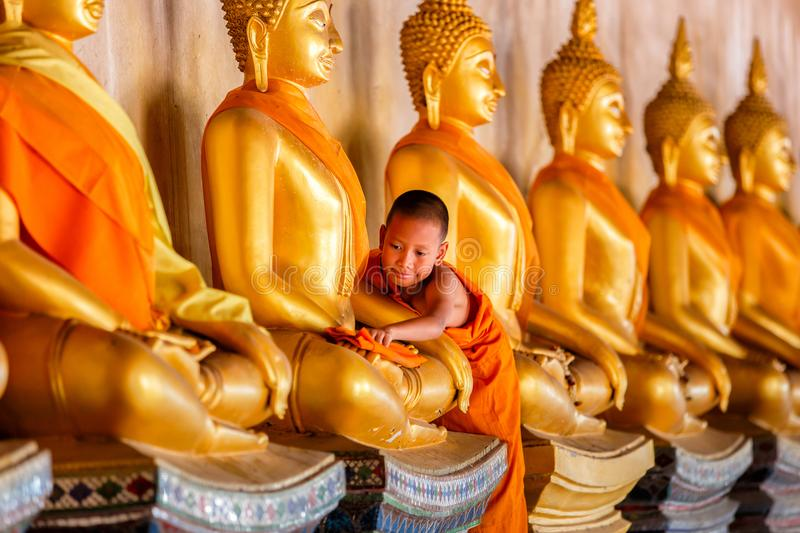 Young Novice monk scrubbing buddha statue at old temple in thailand. Ayuthaya Province royalty free stock photo