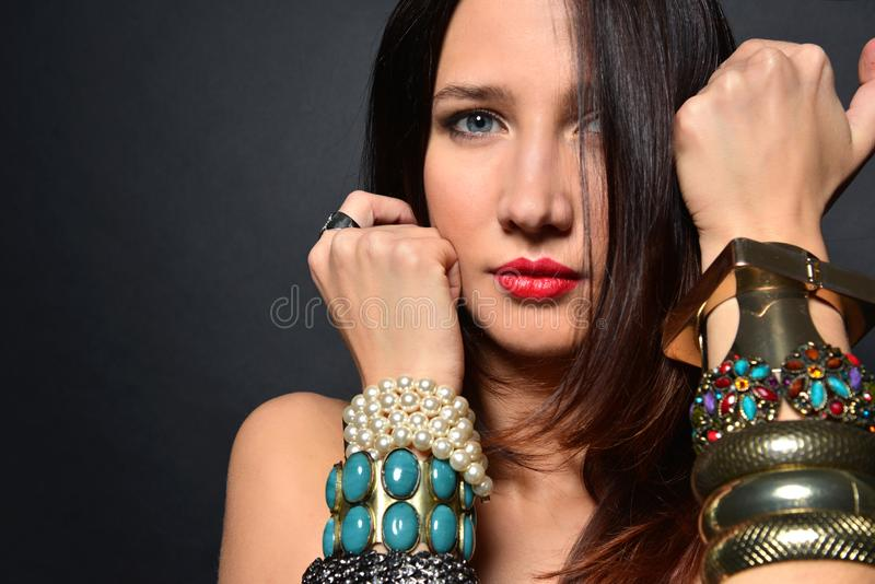 Young brunette lady with luxury accessories isolated on black background. Young nude brunette with flowing hair holds her hands with a lot of beautiful luxury stock photos