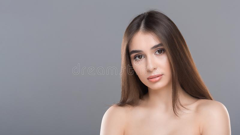 Young nude gorgeous woman portrait, grey panorama background. Ideal of beauty. Young nude gorgeous woman portrait, grey panorama background with empty space royalty free stock photography