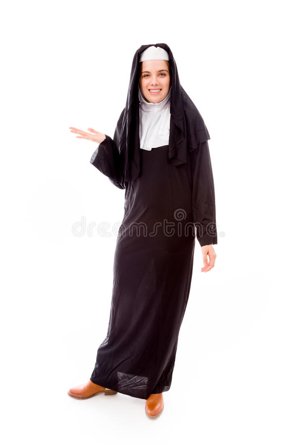 Young nun showing something. Young adult caucasian woman isolated on a white background stock photo